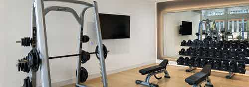AMLI Park Broadway fitness center with free weights and flat screen TV and weight lifting machine and two benches