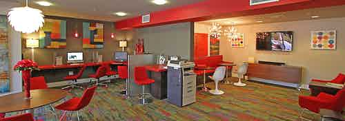 Interior view of AMLI Warner Center business center with computer stations, big screen TV, printer and red lounge seating