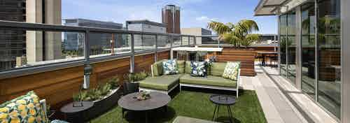 Exterior daytime view of landscaped rooftop lounge with comfortable seating area with pillows and tables overlooking the city