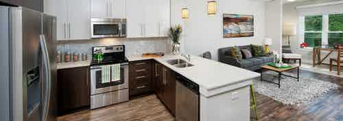 AMLI Piedmont Heights kitchen with stainless steel appliances and both white and dark wood cabinets with light hardwood