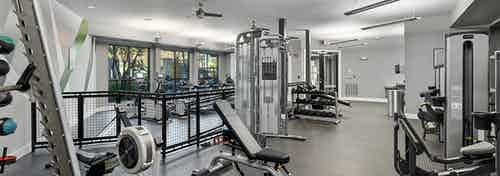 Interior view of the fitness center at AMLI Parkside apartments with weight machines that overlook the treadmills
