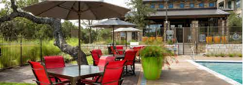 Poolside dining area with dark red seating, white umbrellas, and orange potted plants nearby