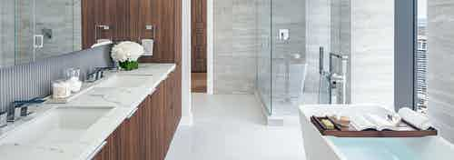 Interior view of AMLI Fountain Place penthouse bathroom with double vanity with dark brown cabinetry and glass shower and tub