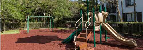 Outdoor children's playground at AMLI Toscana Place featuring stairs for climbing, slide and swings all set on rubber floor