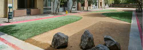Daytime view of Dog Park with gravel trim, grass and esthetic boulders and pet waste station at AMLI Warner Center apartments