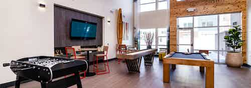 Interior of clubroom with shuffle board, pool table and foosball table and big screen TV at AMLI Littleton Village apartments