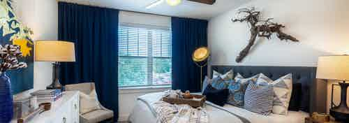 AMLI Grapevine apartment bedroom with gray carpet and a ceiling fan and a large window with blinds and dark blue curtains