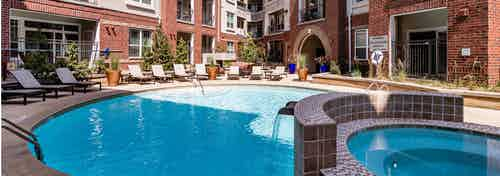 A daytime view of the pool at AMLI Park Avenue apartments with a hot tub and lounge chairs with surrounding trees and plants
