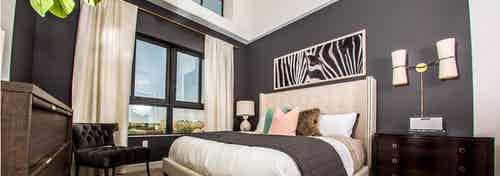 Interior view of an AMLI Joya apartment bedroom with a bed underneath black and white wall art and open window to a sky view