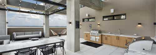 Outside view of AMLI Lenox rooftop with two grills and sink and lots of storage space with multiple seating areas
