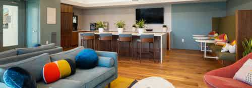 Newly designed clubroom at AMLI South Shore with hardwood flooring and grey walls with blue grey couch and barstool seating