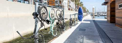 Daytime view of the marina walkway by the boat house, paddleboard rack and bicycle rack at AMLI Marina Del Rey apartments