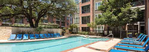 Exterior view of pool on a sunny day at AMLI Eastside with surrounding bright blue lounge chairs and vibrant trees