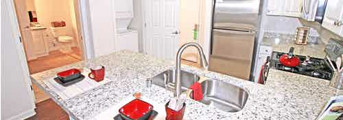 Interior view of AMLI Warner Center apartment kitchen with granite countertops, upgraded cabinets and peek into bathroom area