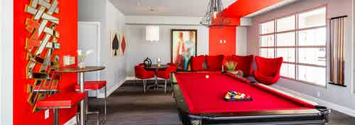 Interior view of the game room at AMLI Arista apartments featuring a pool table and several chairs with a red color scheme