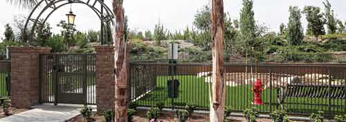 Daytime view of Dog Park's arched entrance with fence, turf and pet waste station at AMLI Spanish Hills apartment building