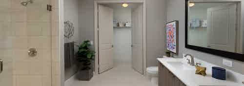 Interior view of AMLI 8800 apartment bathroom with double vanity, mirror, toilet, glass shower enclosure and walk-in closet
