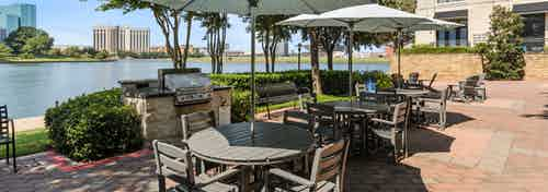 AMLI Las Colinas grilling and dining area shaded by three umbrellas with a view of Lake Carolyn and Las Colinas