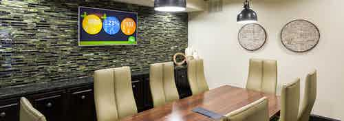 Interior of conference room at AMLI Campion Trail apartment building with wood table and eight chairs and big screen TV