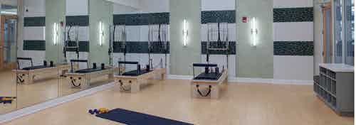 Yoga and Pilates studio at AMLI Evanston with light wood floors and only two exercise machines for maximal open space