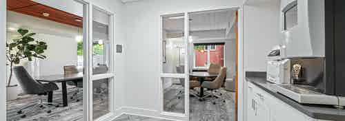 View into two private conference rooms at AMLI Bellevue Park  apartments with Starbucks coffee machine on countertop