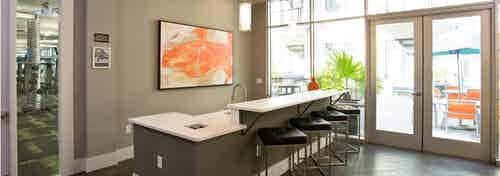 Alternate angle of AMLI 5350 resident lounge with black barstools at a long counter with orange wall art and patio doors