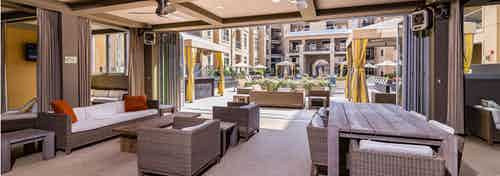 Daytime view of AMLI RidgeGate outdoor lounge with comfortable seating overlooking cabanas and pool area with lush planters