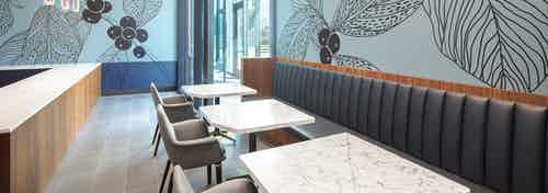 Co working space at AMLI Fountain Place with 3 white tables and long gray booth and blue wall with large brown painted leaves