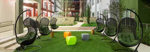 Close up of six green lounge chairs with small colorful tables in the courtyard at AMLI at Mueller at nighttime