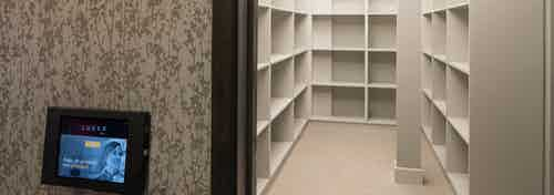 Interior of luxer package amenity at AMLI Deerfield with iPad on outside of doorway and wall to wall shelving inside room