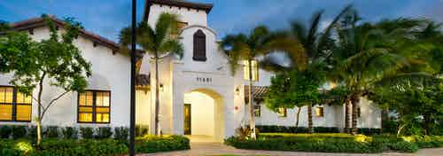 Dusk view of AMLI Doral clubhouse and leasing office white painted front entrance with lush landscaping and street lights
