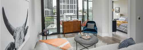 Living room at AMLI Arts Center with floor to ceiling windows overlooking the city and a large wall hanging of a ram
