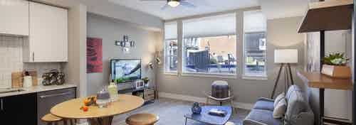 Interior view of AMLI Riverfront Green apartment kitchen and living room with window view of adjacent brick building