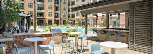 Grill station and 3 small tables with 2 chairs each in AMLI Addison courtyard with pool and cabanas and building in rear