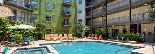Daytime AMLI 300 resort-style swimming pool surrounded by greenery and with orange outdoor lounge seating