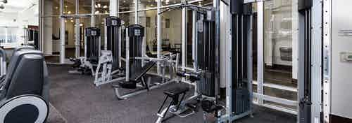 View of the fitness center at AMLI Park Avenue apartments with free weights and other strength training machines with windows