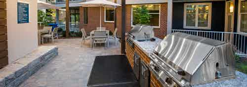 AMLI Buckhead barbecue area with grills and outdoor counter space and stone flooring leading to area with tables and chairs
