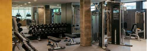 View of fitness center at AMLI Riverfront Green apartments with free weights and other strength training machines