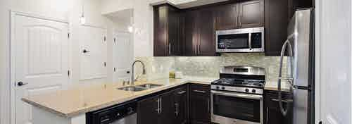 Interior of AMLI Spanish HIlls apartment kitchen with dark cabinetry, granite countertops and stainless steel appliances