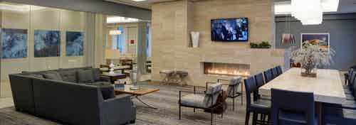 Interior view of AMLI River North clubroom with a large fireplace and an L shaped couch and a high rise table with barstools