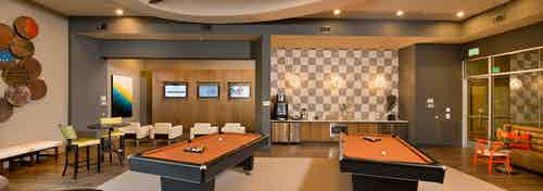 Interior view of AMLI RidgeGate game lounge with checkered backsplash, java bar and two billiards tables and gaming stations