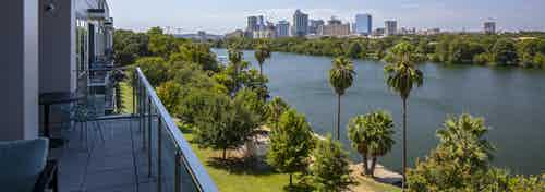 Daytime view of downtown Austin skyline and Lady Bird Lake from AMLI South Shore apartment building balcony with blue chairs