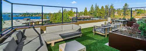 Exterior view of AMLI Bellevue Park rooftop deck with planter and gray couch on green turf and view of Lake Washington