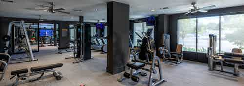 Interior view of AMLI Grapevine fitness center boasting TVs and free weights and strength training and cardio machines