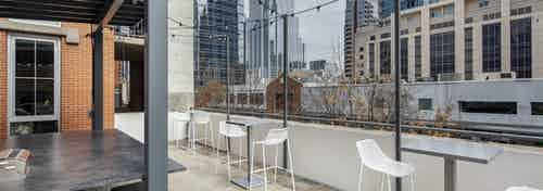 AMLI Downtown outdoor grill deck with white tall chairs and tables and string lights overlooking Austin skyscrapers and trees