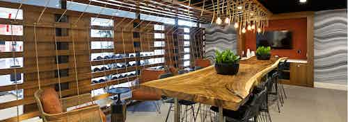 Interior of AMLI Marina Del Rey apartment workout rest area with live edge wood slab table and bulb rope pendant lighting