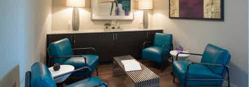 AMLI on Aldrich office with teal leather chairs around a small coffee table with two lamps sitting on counter in background