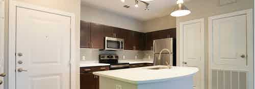 Redesigned kitchen at AMLI Inverness apartments with espresso cabinets and white granite counter tops and overhead lighting