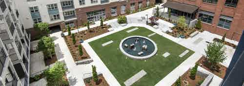 Aerial daytime view of the AMLI Decatur grassy and landscaped courtyard encircled by the apartment and office buildings