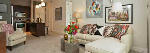 Living room at AMLI 5350 with carpet floors and colorful throw pillows on a white sofa with peek into kitchen in background
